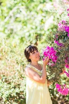 Plenerowy portret młoda piękna modna dama pozuje blisko kwiatonośnego drzewa. dziewczyna patrzy na bok.