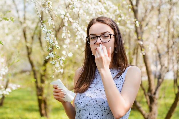 Plenerowy portret młodej dziewczyny z alergią na pyłki sezonowe, używa chusteczki do nosa i sprayu do nosa, pozuje nad kwitnącym drzewem, ma katar i kichanie. koncepcja ludzi i chorób