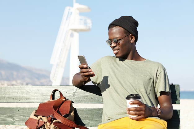 Plenerowy portret modnego uśmiechniętego turysty afroamerykanów popijających kawę z papierowego kubka i szukających nowych ciekawych miejsc na stronach internetowych za pomocą aplikacji online na telefon