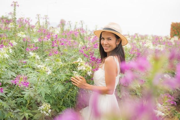 Plenerowy portret piękna w średnim wieku asia kobieta. atrakcyjna dziewczyna w polu z kwiatami
