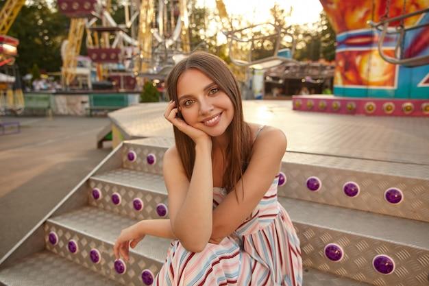 Plenerowy portret pięknej młodej brunetki kobiety w pozytywnym nastroju, trzymając głowę z dłonią, siedząc na schodach nad parkiem z atrakcjami, uśmiechając się lekko