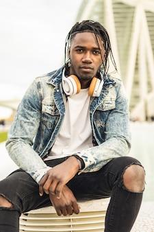 Plenerowy portret przystojny i atrakcyjny młody afrykański mężczyzna z muzycznymi hełmofonami na ulicie