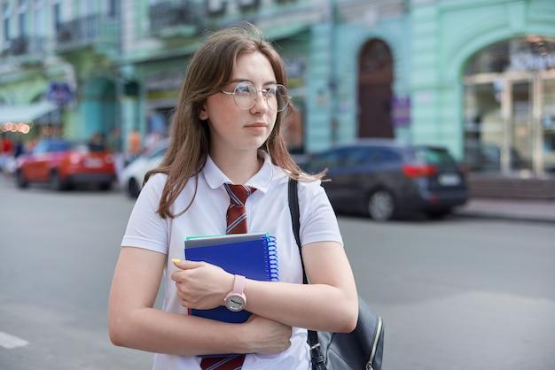 Plenerowy portret studentki uniwersytetu, pewna siebie kobieta pozuje w białej koszulce, okularach, krawacie, plecaku
