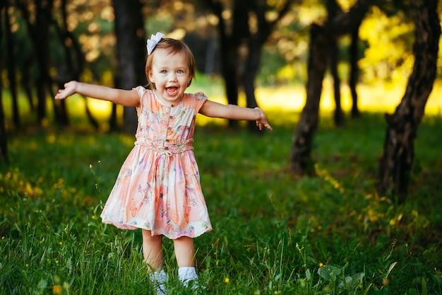 Plenerowy portret urocza uśmiechnięta mała dziewczynka w letnim dniu