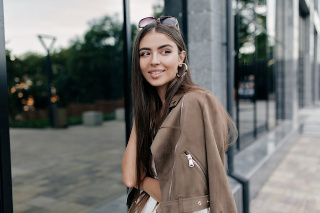 Plenerowy portret uroczej ślicznej kobiety o długich ciemnych włosach i cudownym uśmiechu spędza wolny czas w parku i czekając na przyjaciół