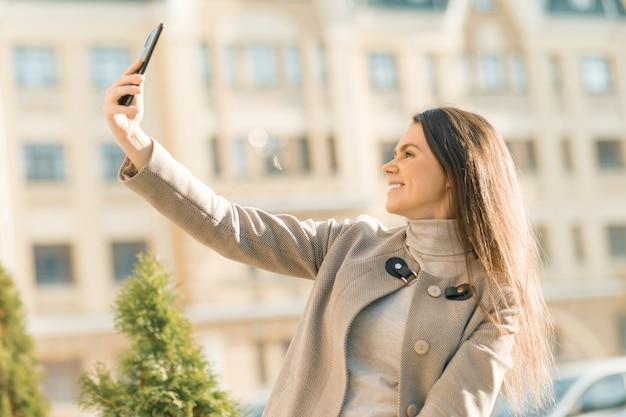 Plenerowy portret uśmiechnięta szczęśliwa młoda kobieta z smartphone