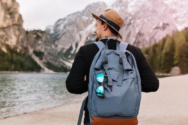 Plenerowy portret z tyłu męskiego turysty niosącego duży zdobiony plecak i spacerującego w góry rano