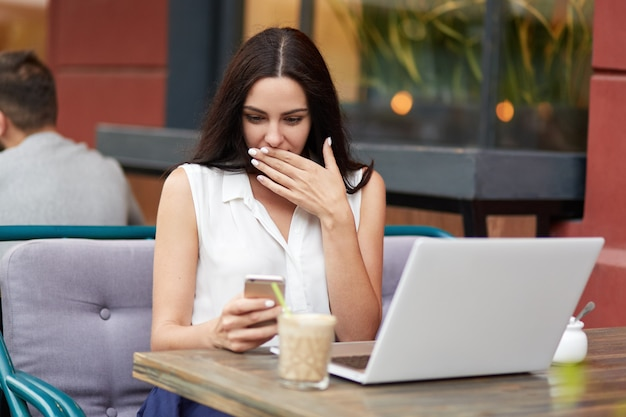 Plenerowy portret zdziwiona brunetki kobieta gapi się na ekran telefonu komórkowego, gdy otrzymuje nieoczekiwaną wiadomość, pracuje na komputerze przenośnym