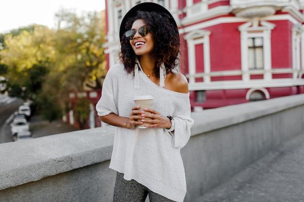 Plenerowy pozytywny wizerunek uśmiechnięta ładna murzynka w białym pulowerze i czarnym kapeluszu trzyma filiżankę kawy. tło miejskie.