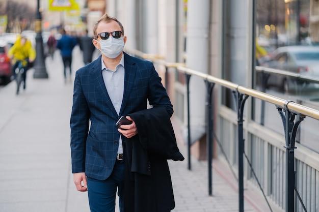 Plenerowy strzał biznesmen w formalnym ubraniu, trzyma w rękach nowożytny telefon komórkowy, chodzi po ulicy, chroni się maską medyczną