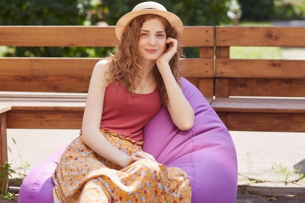 Plenerowy strzał młoda kobieta siedzi na dużym purpurowym miękkim bezramowym krześle na świeżym powietrzu, atrakcyjna kobieta ma na sobie t-shirt burgunde, spódnicę i kapelusz, odpoczywa z przyjaciółmi w miejskim parku.