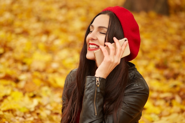 Plenerowy strzał młoda szczęśliwa kaukaska ciemnowłosa kobieta z smartphone, powabna dama siedzi na ziemi otaczającej żółtych liście, jest ubranym skórzaną kurtkę i czerwonego beret.