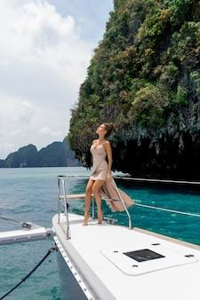Plenerowy strzał urocza młoda kobieta w beż sukni sukni stoi na krawędzi jachtu