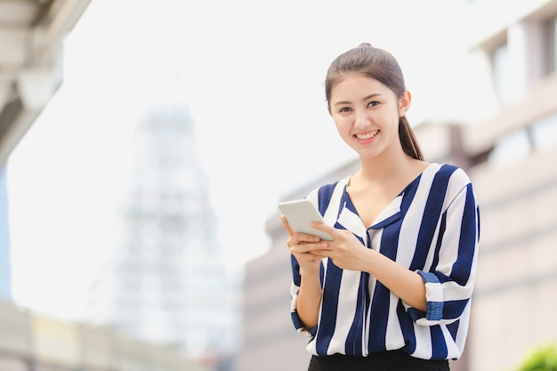 Plenerowy styl życia młoda kobieta patrzeje na smartphone.