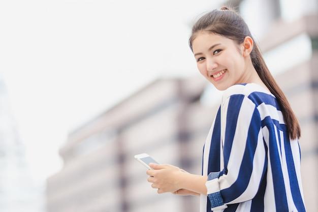 Plenerowy styl życia młody bizneswoman patrzeje na smartphone. pomysł na biznes