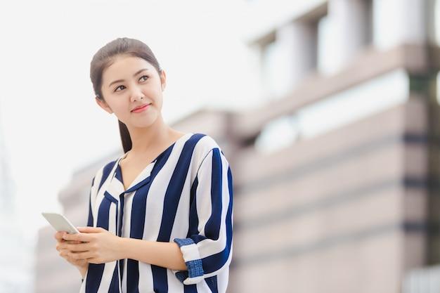Plenerowy styl życia młody bizneswoman patrzeje na smartphone
