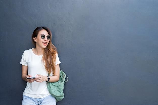 Plenerowy stylu życia portret ładna seksowna młoda azjatykcia dziewczyna w podróży i szkła projektujemy na szarości ścianie