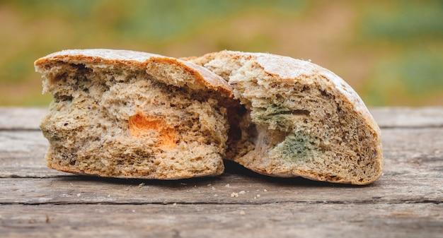 Pleśń na kromce chleba, leżącej na drewnianej powierzchni.