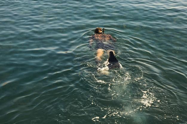 Płetwonurek z pistoletem włóczni unoszącym się na powierzchni morza
