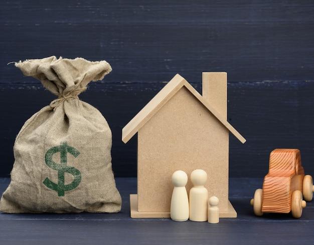 Płócienna torba pełna pieniędzy i drewnianego domu. koncepcja kupna nieruchomości, wynajmu.