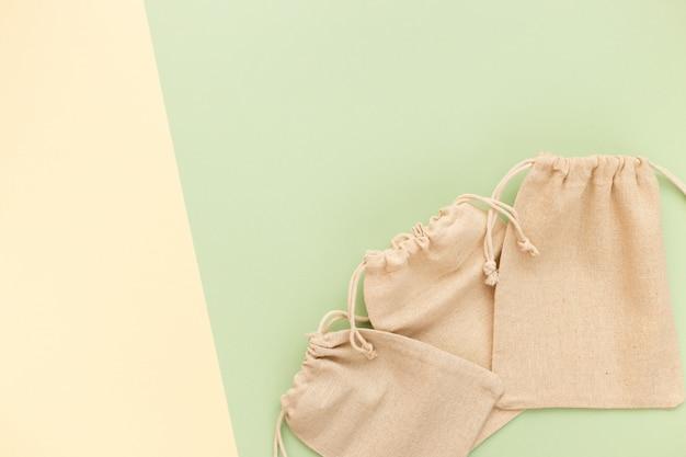 Płócienne torby ze sznurkiem, makieta małego ekologicznego worka wykonanego z tkaniny z naturalnej bawełny na zielonym pastelowym kolorze