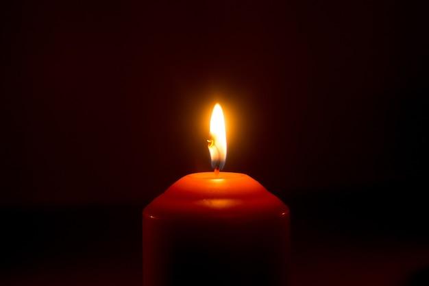 Płomień świecy na ciemnej powierzchni