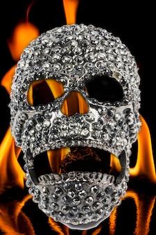 Płomienie ognia na czarnym tle z metalową maską