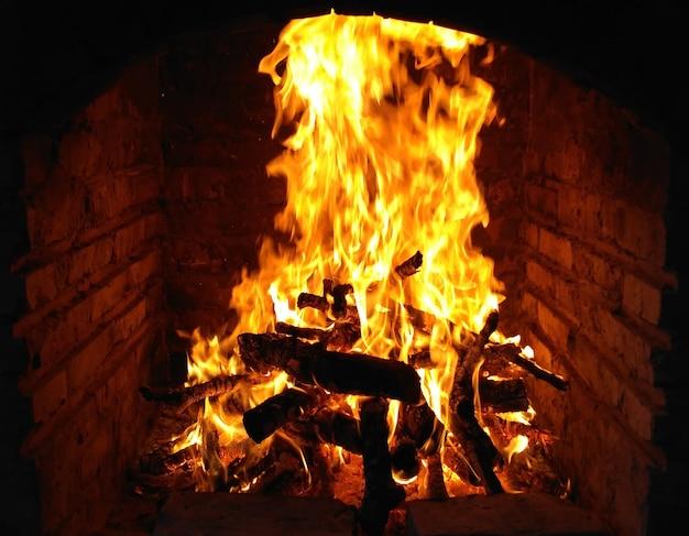 Płomienie ognia w piecu na ognisko izolowane z balck bal