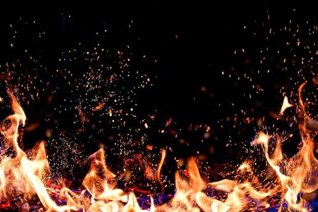 Płomienie ognia z bliska na ciemnym tle. skopiuj miejsce, umieść tekst.