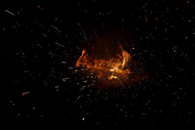 Płomienie ognia z iskrami na czarnej powierzchni
