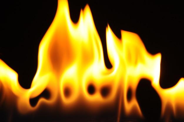 Płomienie palnika alkoholowego na ciemnej ścianie z bliska