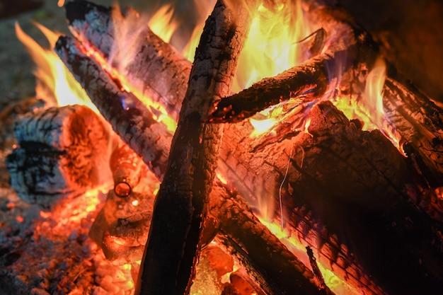 Płomienie z ogniska w nocy. przygodowy styl życia. koncepcja wędrówki. aktywne wakacje weekendowe dzikiej przyrody na świeżym powietrzu.