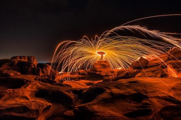 Płonąca stalowa wełna na skale blisko rzeki przy sam phan bok w ubonratchathani niewidziany w tajlandia. wielki kanion tajlandii.