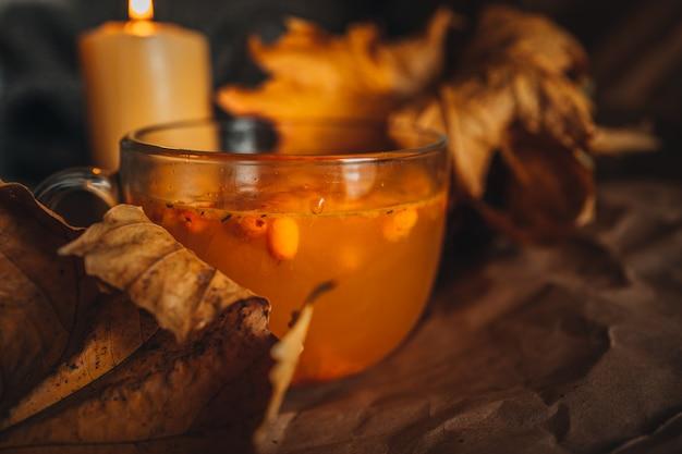 Płonąca świeca i duży kubek gorącej pomarańczowej herbaty z rokitnika w przytulny domowy jesienny wieczór