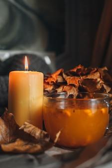 Płonąca świeca i kubek gorącej pomarańczowej herbaty z rokitnika w przytulnym domowym jesiennym wieczorze