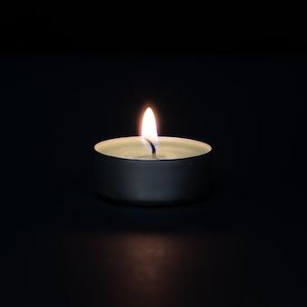 Płonąca świeca na ciemnej ścianie z flarą na pierwszym planie.