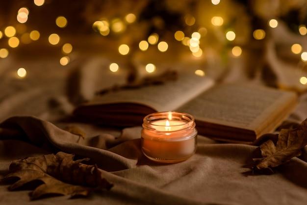 Płonąca świeca na drewnianym stole przed książką w półmaszcie. uczenie się. studiowanie biblii