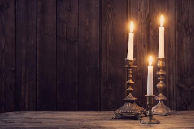 Płonąca świeca na starym ciemnym drewnianym