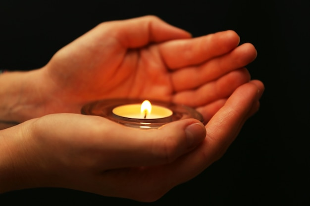 Płonąca świeca w dłoniach na ciemnej powierzchni