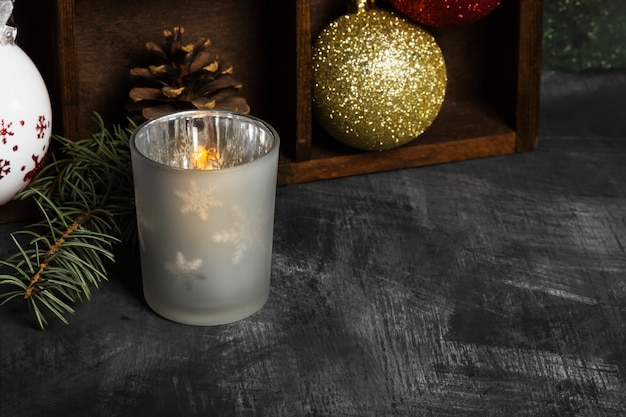 Płonąca świeca w świecznikach i atrybutach świątecznych na ciemnej powierzchni