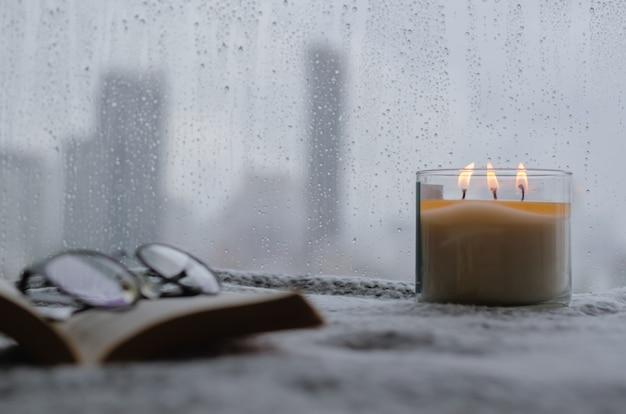 Płonąca świeca zapachowa stawia w pobliżu okna, które ma kroplę deszczu w sezonie monsunowym z rozmytym tłem miasta. koncepcja zen i relaks.