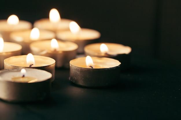 Płonąca świeczka na stole w ciemności, miejsce na tekst. symbol pogrzebu