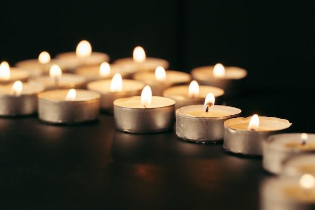 Płonąca świeczka na stole w ciemności, przestrzeń dla teksta. symbol pogrzebu