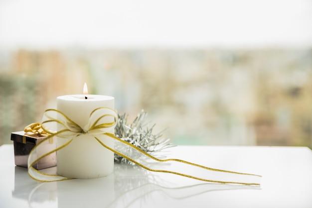 Płonąca świeczka z kokardą w pobliżu okna