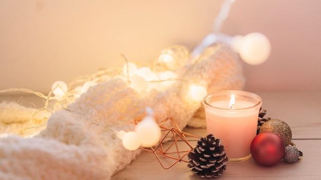Płonąca świeczka z szalikiem na stole