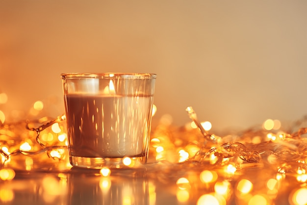 Płonąca świeczka z złotą girlandą zaświeca w bokeh na ciemnym tle