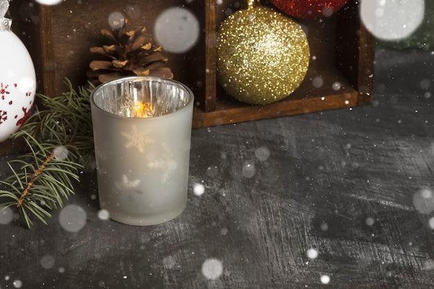 Płonącą świeczkę w świeczniki i atrybuty bożego narodzenia na ciemne, miejsce, śnieg
