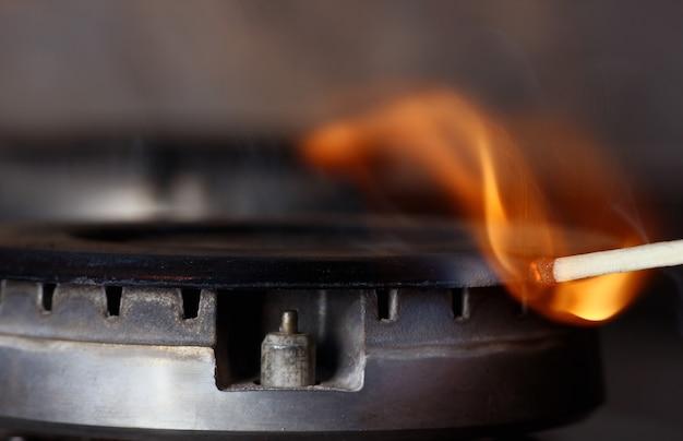 Płonąca zapałka, która zapala gaz w kuchence gazowej