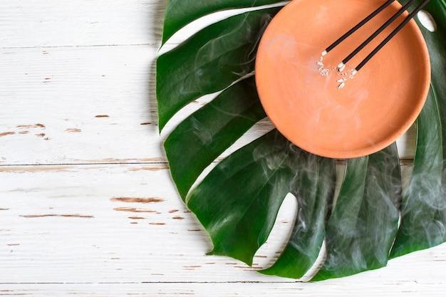 Płonące aromatyczne kadzidełka. ceramiczne naczynie i liść potwora.