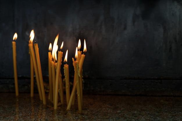 Płonące cienkie świeczki na czarnym tle w świątyni